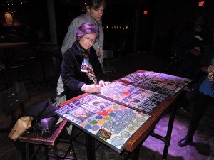 Bonnie MacLean signs copies of the poster she created to commemorate the opening of the Philadelphia Fillmore. With Bonnie is her son, David Graham. (Photo by Mike Morsch)